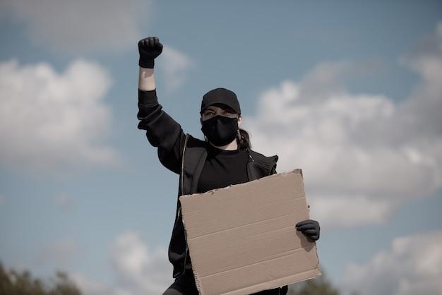 Une femme protestante lève la main en l'air, tenant une affiche avec l'inscription contre le ciel