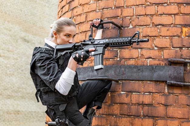 Femme puissante tenant le pistolet. style de film d'action de guerre