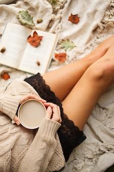 Femme en pull chaud et plaid à carreaux avec une tasse de café au lait dans les mains, assis avec livre