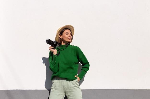 Femme en pull décontracté vert et chapeau en plein air sur mur blanc heureux touriste positif avec appareil photo professionnel