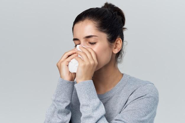 Femme en pull gris écoulement nasal problèmes de santé infection