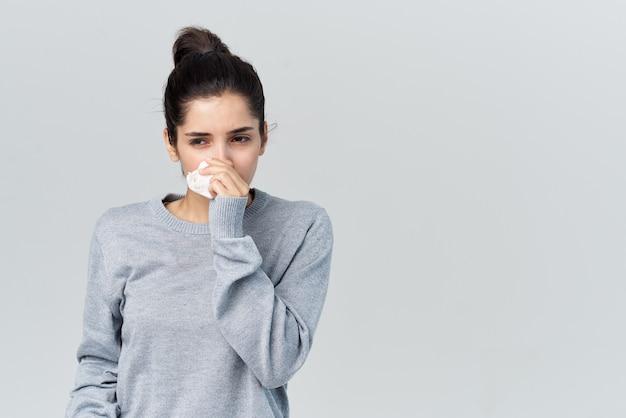 Femme en pull gris s'essuie le visage avec un mouchoir problèmes de santé