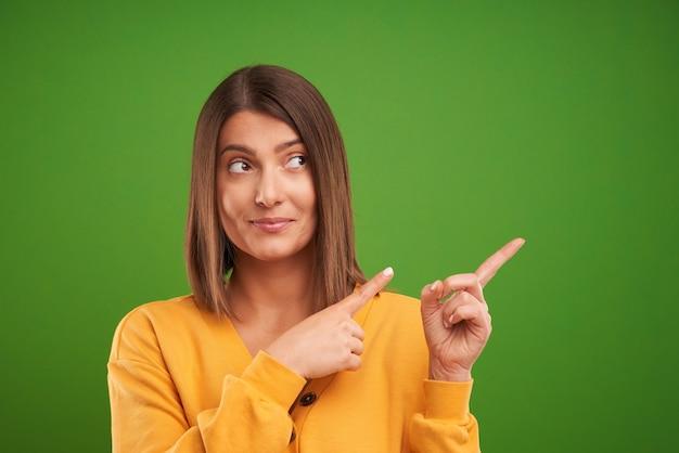 Femme en pull jaune pensant et pointant sur fond vert