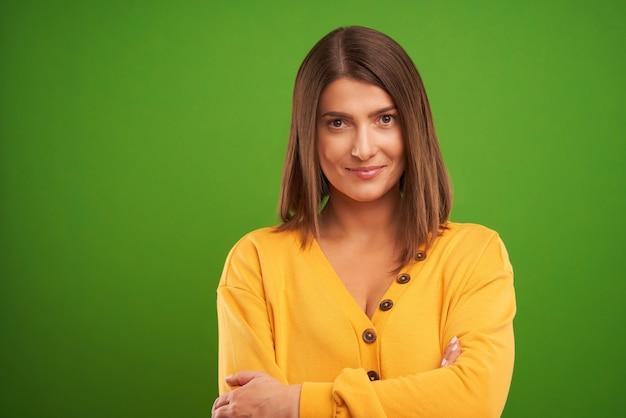 Femme en pull jaune regardant la caméra sur fond vert
