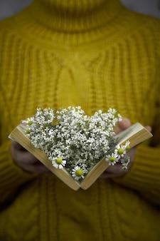 Une femme en pull jaune tricoté tient un livre avec des marguerites à l'intérieur d'une main féminine avec un objet bouquet de wi...
