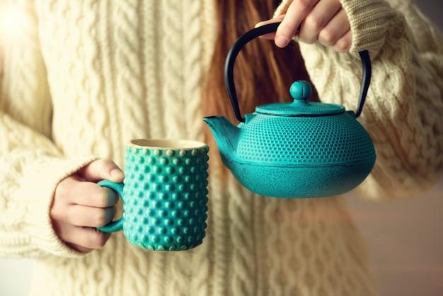Femme en pull de laine tricoté avec une théière turquoise et des tisanes dans une tasse à la main.