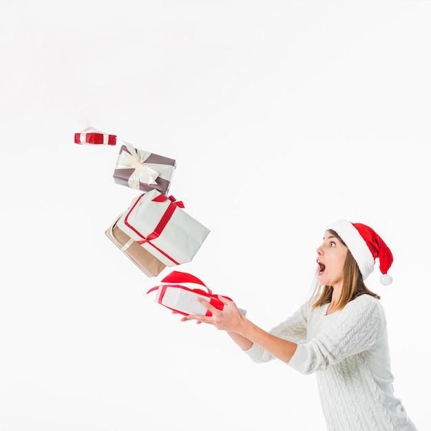 Femme en pull laissant tomber des coffrets cadeaux