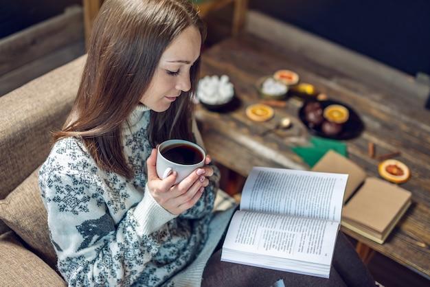 Femme en pull lisant un livre avec une tasse de café le soir dans une ambiance chaleureuse de noël. ambiance confortable pour le nouvel an