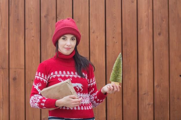 Femme en pull de noël avec arbre de noël et cadeau sur mur en bois