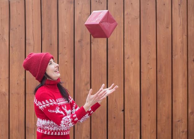 Femme en pull de noël attraper un cadeau de noël volant sur un mur en bois