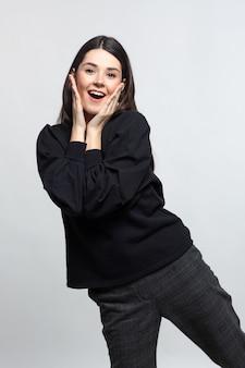 Femme en pull noir fait preuve de joie