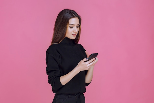 Femme en pull noir tenant un smartphone et envoyer des sms ou vérifier les médias sociaux.