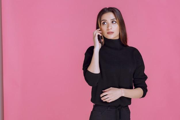 Femme en pull noir tenant un smartphone à l'oreille et parler.