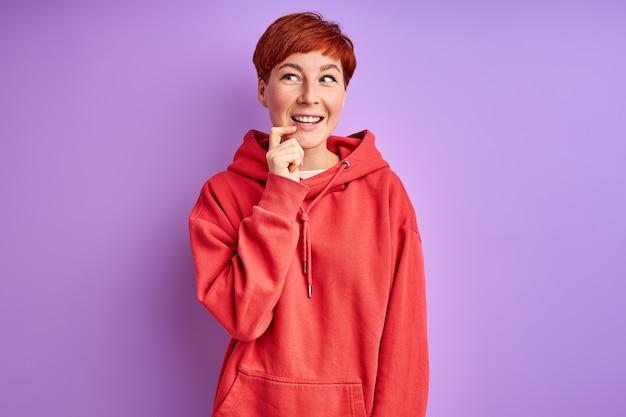 Femme en pull-over rouge penser en contemplation, isolé sur mur violet. en pensées