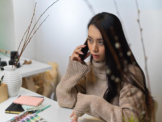 Femme en pull parler au téléphone