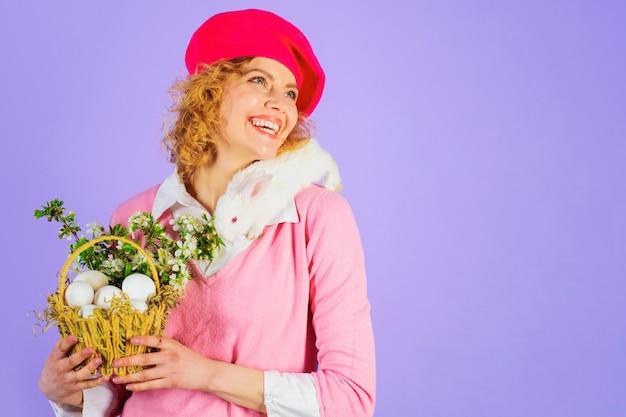 Femme avec pull rose et chapeau rose vif tenant un panier avec des oeufs de pâques et des plantes sur fond violet.