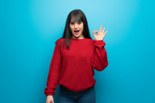 Femme, à, pull rouge, sur, bleu, mur, surpris, montrer, signe ok