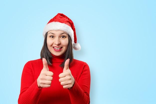 Femme en pull rouge et chapeau de noël sur fond bleu