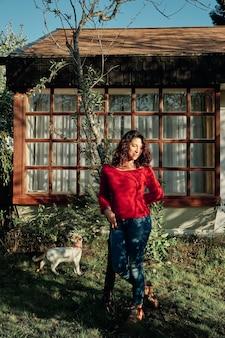Femme avec pull rouge et cheveux bouclés pose sur un arbre à côté de son animal de compagnie dans le jardin de sa maison