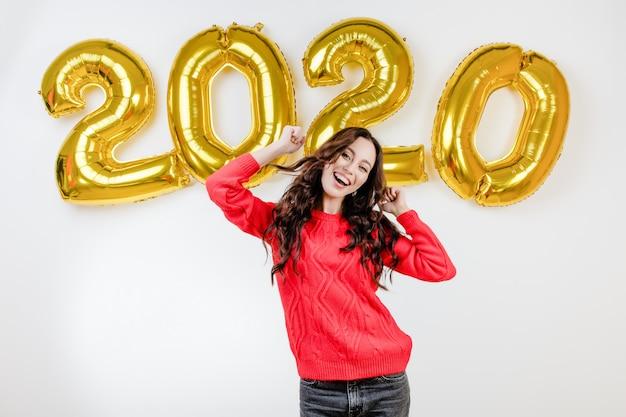 Femme en pull rouge dansant devant les ballons du nouvel an 2020
