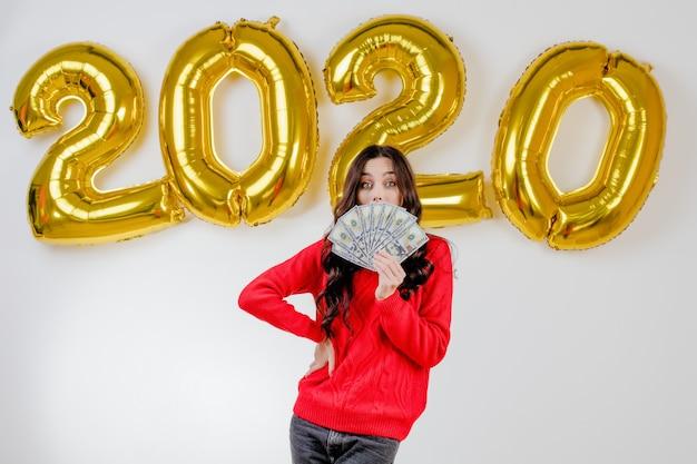 Femme en pull rouge détenant des billets de cent dollars devant des ballons du nouvel an de 2020