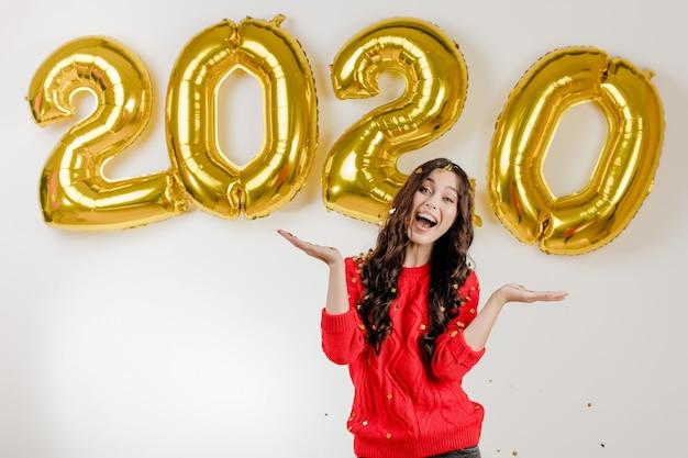 Femme en pull rouge jetant des confettis d'argent dans les airs devant des ballons du nouvel an 2020