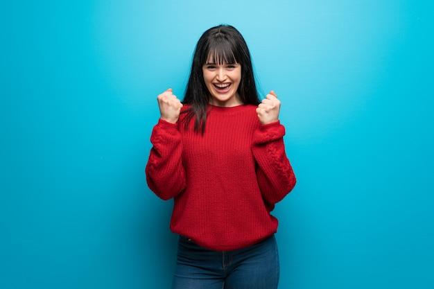 Femme avec un pull rouge sur un mur bleu célébrant une victoire en position de vainqueur