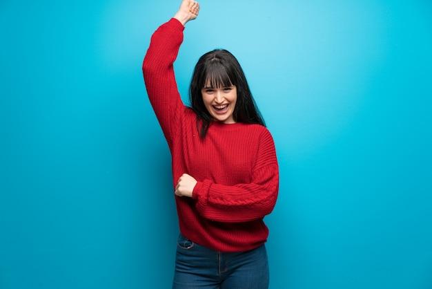 Femme, pull rouge, mur bleu, célébrer, victoire