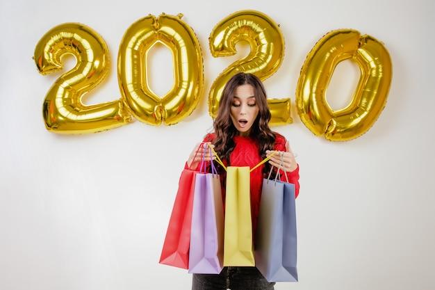 Femme en pull rouge ouvrant des sacs colorés devant des ballons de nouvel an 2020