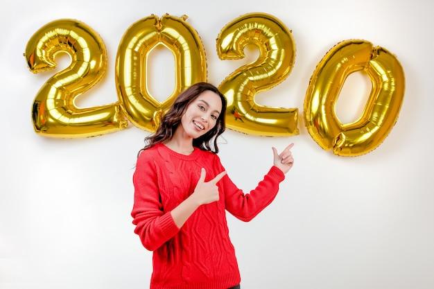 Femme en pull rouge pointant vers les ballons du nouvel an 2020