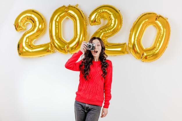 Femme en pull rouge prenant des photos avec l'appareil photo vintage devant des ballons du nouvel an 2020