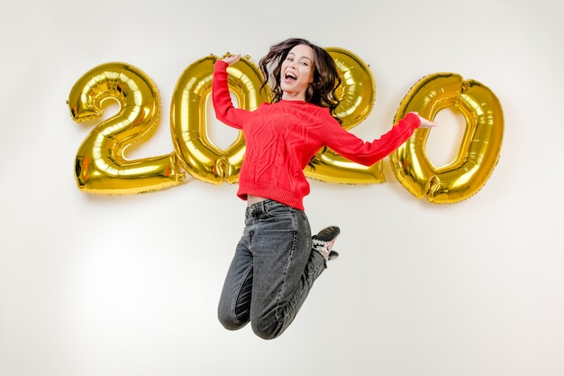Femme en pull rouge sautant haut dans les airs devant des ballons du nouvel an 2020