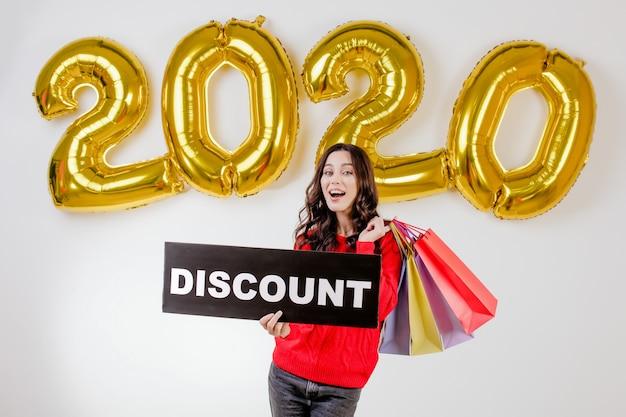 Femme en pull rouge tenant des sacs colorés et signe de réduction de surface devant 2020 ballons de noël