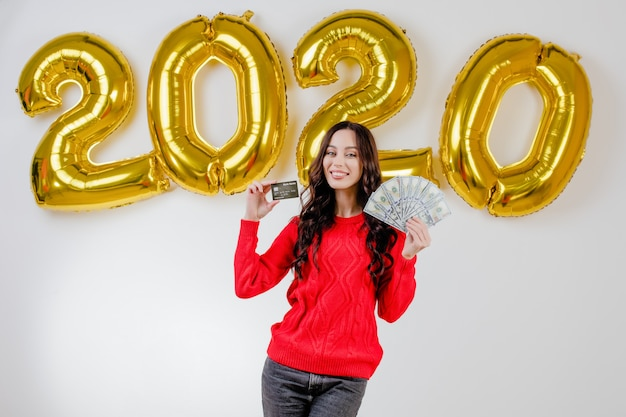 Femme, pull rouge, tenue, argent, carte crédit, devant, ballons, nouvel an 2020