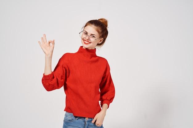 Femme en pull rouge tient la main devant ses lunettes de maquillage amusant