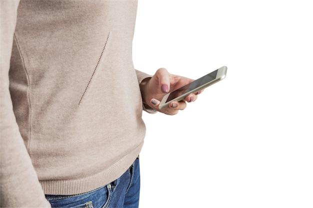 Femme en pull en tricot marron et jeans bleu tenant un smatphone blanc à la main avec une manucure tendance. isolé sur fond blanc