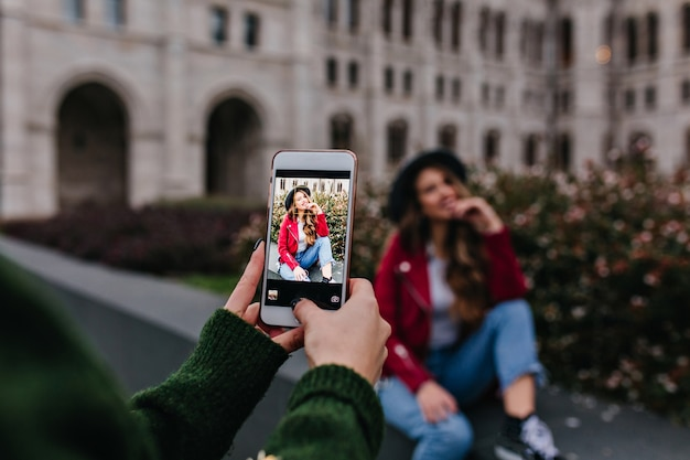 Femme en pull vert à la mode en prenant une photo de sa sœur assise à côté