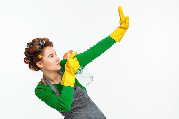 Femme pulvérisant des fenêtres et posant avec du caoutchouc jaune sur les mains