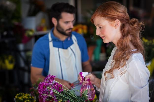 Femme, pulvérisation, eau, bouquet, fleurs, quoique, homme, préparer, fleur, bouquet