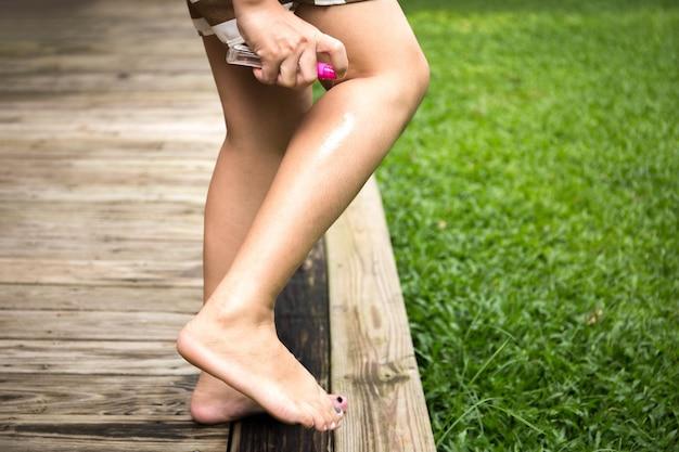 Femme, pulvérisation, insectifuge, elle, jambe