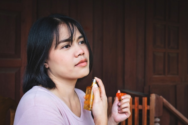 Femme pulvérise du parfum sur son cou