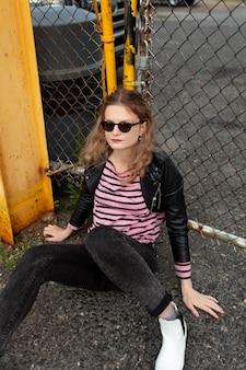 Femme punk avec des lunettes de soleil en milieu urbain