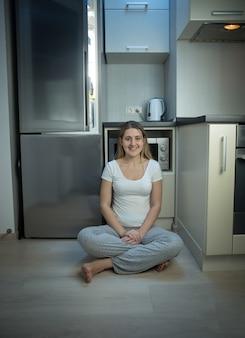Femme en pyjama assis par terre dans la cuisine à côté d'un réfrigérateur ouvert en fin de soirée