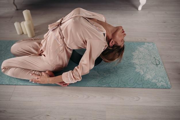 Femme en pyjama assise sur le tapis et faisant un backbend pendant les exercices du matin à la maison. concept de mode de vie sain. remise en forme du matin