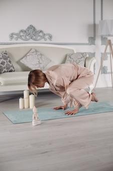 Femme en pyjama faisant des exercices de yoga dans le salon de son appartement tout en appuyant les mains sur le tapis. concept de mode de vie sain. remise en forme du matin