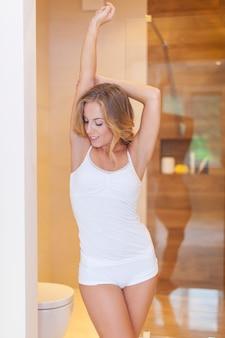 Femme en pyjama qui s'étend dans la salle de bain