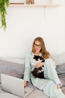 Femme en pyjama travaillant à domicile sur ordinateur portable tout en tenant le chat