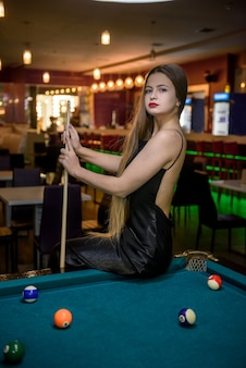 Femme avec queue assis sur une table de billard