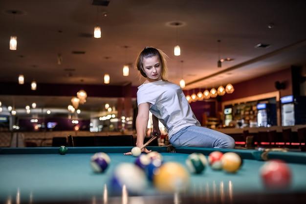 Femme avec queue assise sur une table de billard et posant