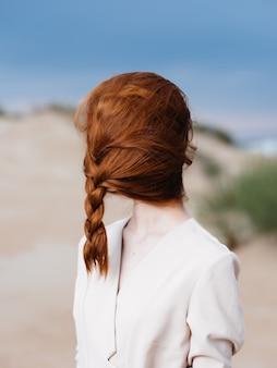 Femme avec queue de cochon sur son visage en manteau sable nature air frais